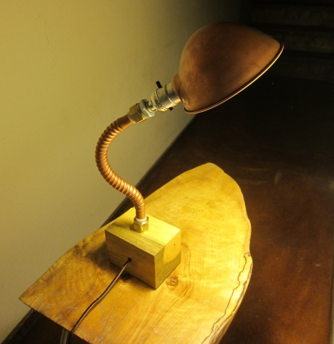 Reused corrugated copper pipe and scrap wood with vintage, copper finished, lamp shade.